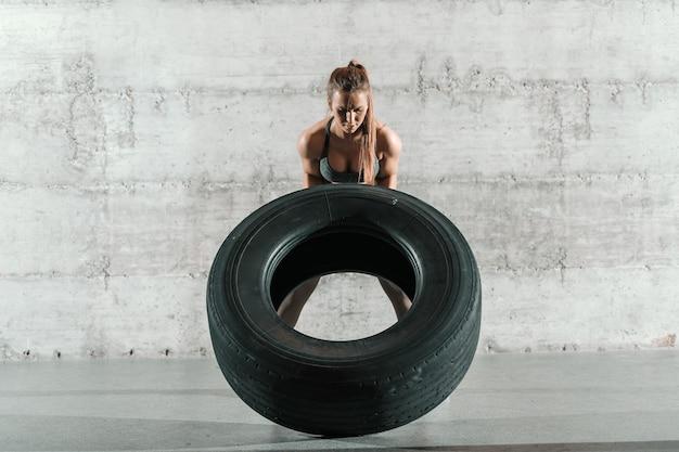 Сильная преданная женщина-культуристка переворачивает шину в тренажерном зале для кроссфита.