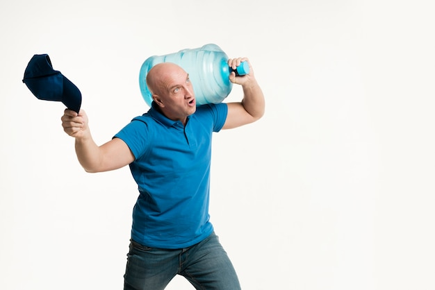 Strong delivery man carrying water bottle