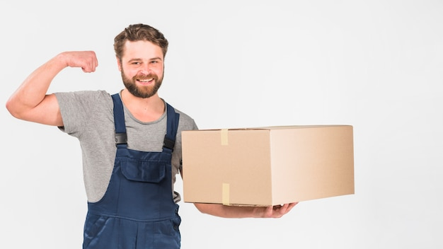 Strong delivery man standing with big box