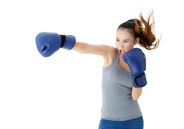 白い背景に空気を打つとパンチする青いボクシンググローブの強い決意の若いアジアの女性