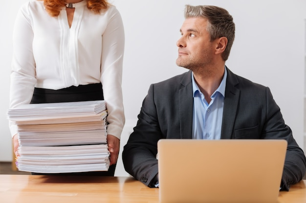 Strong diligent pretty lady holding a pile of papers businessman needing reviewing by the end of the working day