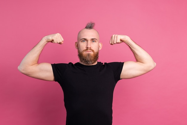 Strong european man on pink background showing muscles