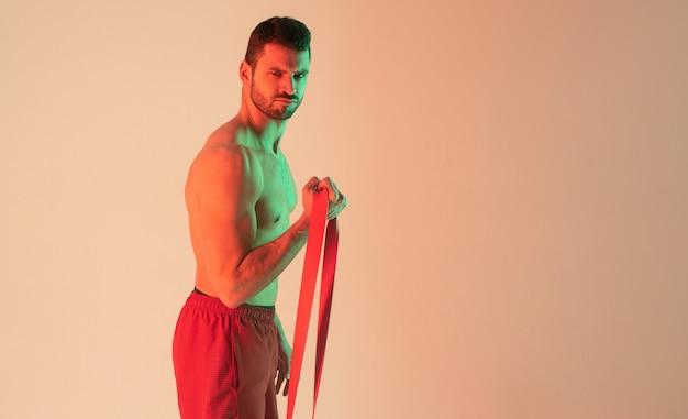 Сильный европейский спортсмен делает упражнения с лентой сопротивления. молодой красивый бородатый мужчина с обнаженным спортивным торсом. изолированные на бежевом фоне с зеленым светом. студийная съемка. копировать пространство