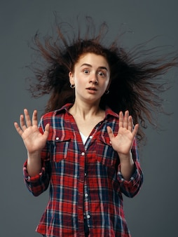 Strong fan blowing in female face, funny emotion. powerful air flow blows on girl in a shirt, black background