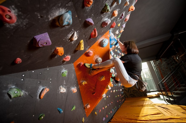 Strong female climber on boulder climbing wall indoor