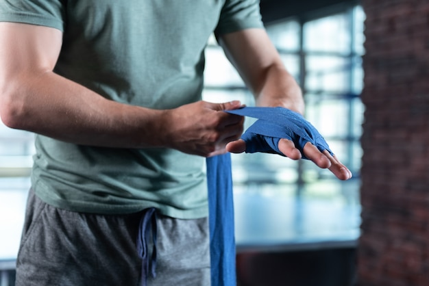 Strong fighter. strong muscle fighter wearing grey shorts and khaki shirt rolling his hands in wrist wraps