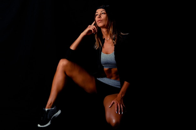 黒の背景にダンベルを持つ強いフィットの女性。セクシーなボディービルダーの肖像画。控えめな画像。