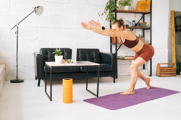 運動マットの上に裸足で立って運動をしているスポーツウェアを身に着けている完璧な運動体を持つ強いフィットの若い女性。健康的なライフスタイルと家庭での身体活動の概念。