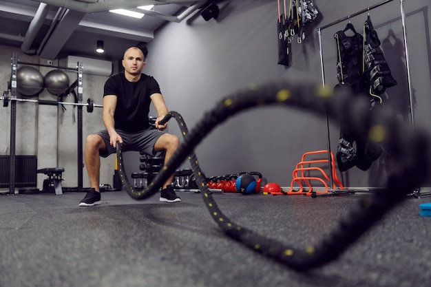 Strong fitness man working out with two battle ropes