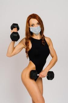 멸균 마스크가 있는 운동복을 입은 강한 피트니스 스포티 여성. 운동 동기 부여 라이프 스타일 개념입니다.