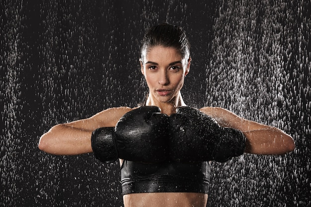 Strong fitness woman fighter 20s in sportswear keeping black boxing gloves together while training under rain drops, isolated over dark background