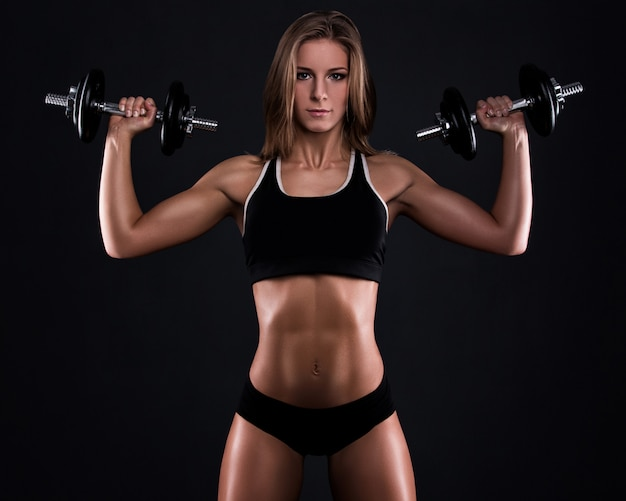 Strong fitness woman with dumbbells