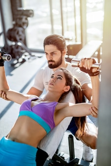 Strong focused personal fitness trainer helping his female client to do weight exercises correct.