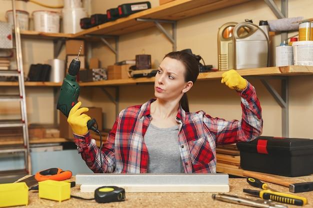 格子縞のシャツと灰色のtシャツを着た、とても楽しい白人の若い茶色の髪の女性が、テーブルの場所で大工のワークショップで働いて、家具を作りながら鉄と木片にドリル穴を開けます。