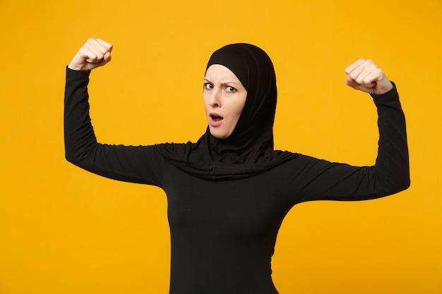 黄色の壁、肖像画で隔離された上腕二頭筋を示すヒジャーブの黒い服を着た強く楽しい若いアラビアのイスラム教徒の女性。人々の宗教的なライフスタイルの概念。