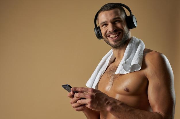 Сильный смешной спортсмен с наушниками позирует перед камерой в студии
