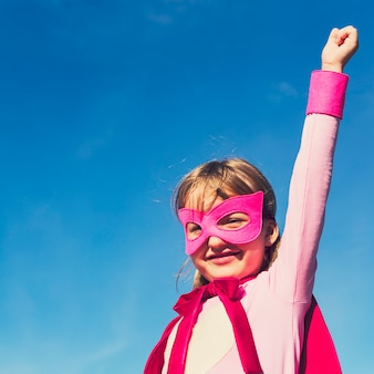 Strong girl in pink superhero outfit
