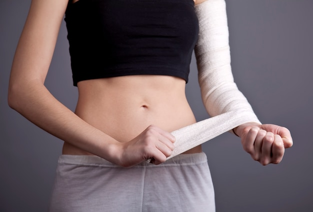 Strong girl's body with with elastic bandage on hand.