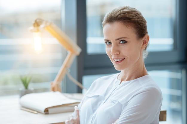 強い視線。笑顔であなたを見ながら楽観を表現する楽しいマネージャーのクローズアップ