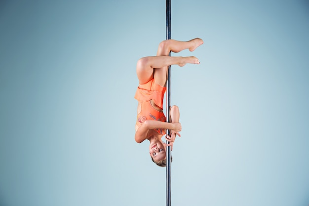 The strong and graceful young girl performing acrobatic exercises on pylon