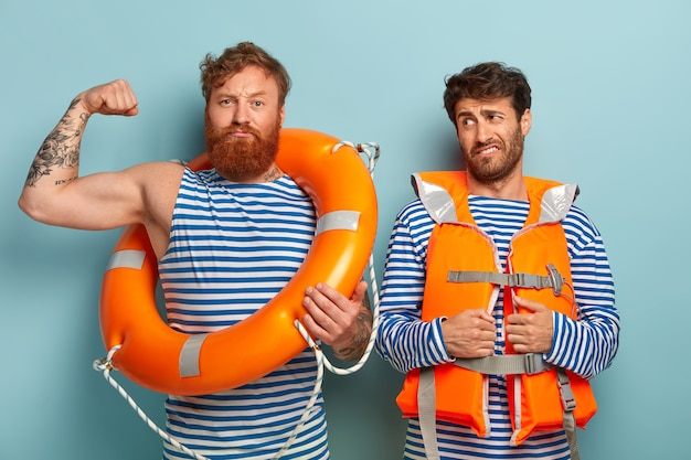 Strong guys posing at the beach with lifejacket and lifebuoy