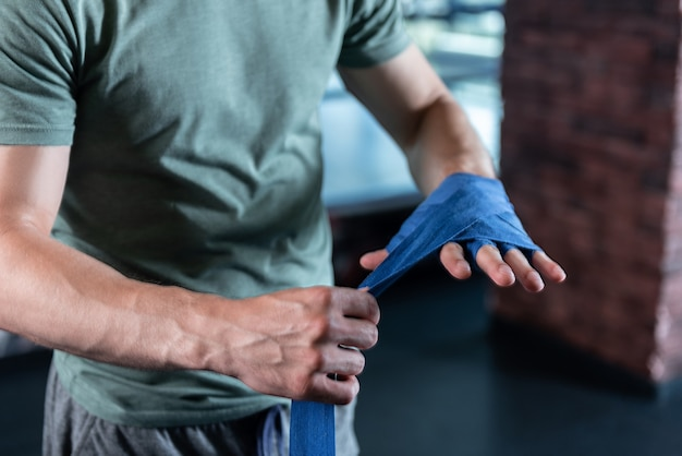 Strong hands. close up of strong hands of sportsman training in gym using long blue wrist wraps