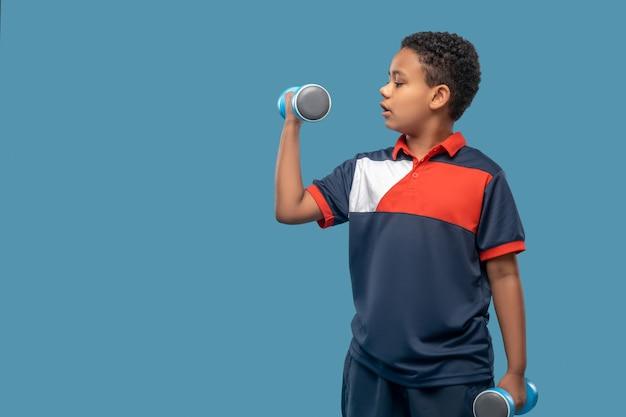 강한 손. 손에 아령을 들고 운동을 하 고 스포츠 tshirt에서 심각한 관련 된 아프리카 계 미국인 소년