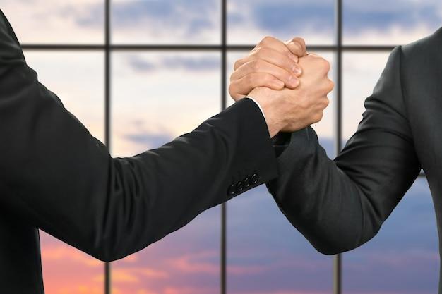ビジネスマンの強い握手。友達&#39;日の出の背景に挨拶。パートナーシップと保護。ジェスチャーの強さ。