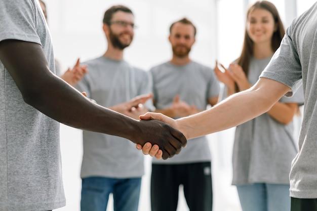 国籍の異なる2人の学生の強い握手