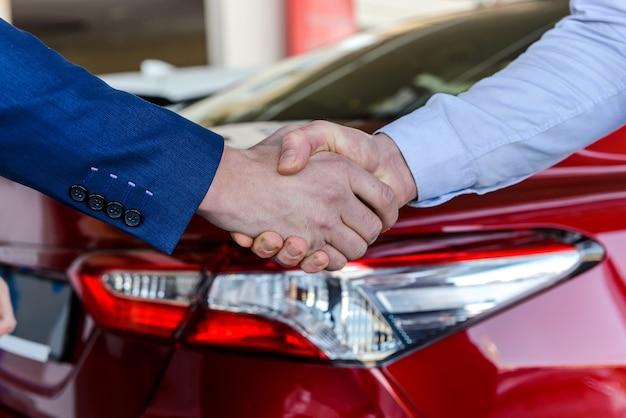 車の背景に強い握手。車の購入取引