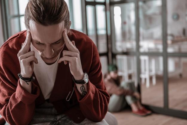 Сильная головная боль. парень в ручных часах испытывает сильную головную боль после эмоционального конфликта