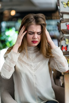 Strong headache is very problematic. beautiful young girl in restaurant.