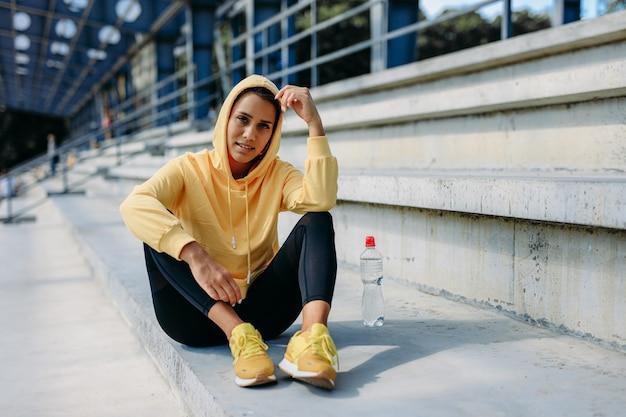 水のボトルと階段に座っている黄色のパーカーと黒のレギンスの強い健康的なブルネット。定期的なトレーニングの後、新鮮な空気で休んでいる若い女性。