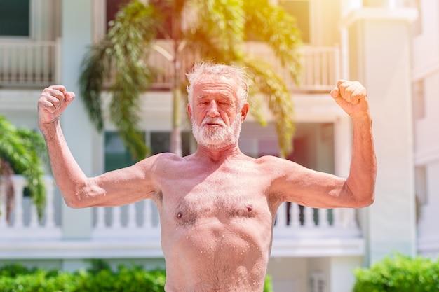 Сильный здоровый пожилой мужчина показывает мускулистое и подтянутое выражение на открытом воздухе