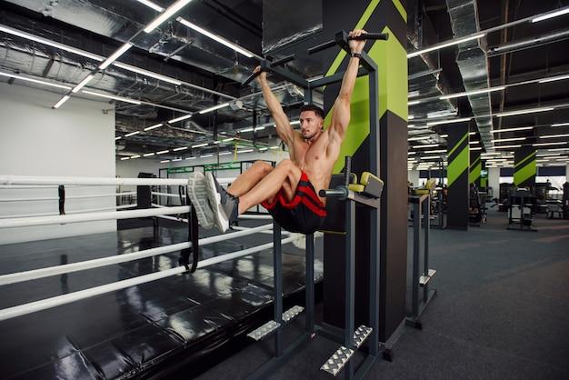 검은 색과 녹색 인테리어가있는 현대적인 체육관에서 훈련하는 동안 크로스바에서 복부 운동을하는 강한 건강한 사람.