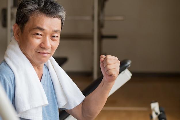 강하고, 건강하고, 행복하고, 웃고, 긍정적 인 수석 웰빙 체육관에서 운동하는 아시아 사람