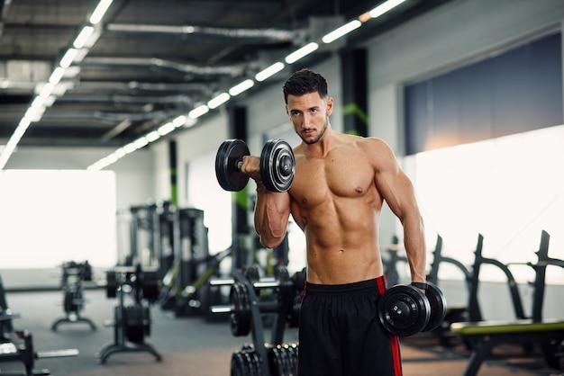 현대 체육관에서 훈련에 아령으로 팔뚝 운동을 하 고 강한 건강 한 남자.
