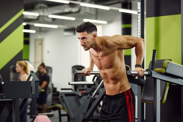 현대적인 체육관에서 훈련하는 동안 평행 막대에 팔 굽혀 펴기를하고 강한 건강 한 남자. 스포티하고 건강한 개념. 돌리 샷.
