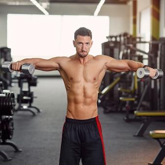 체육관에서 그의 어깨를 훈련 강한 건강 한 남자. 삼각근 근육 훈련을위한 격리 된 운동. 현대적인 체육관에서 운동하십시오.;