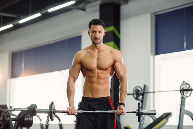 팔뚝을위한 바벨 체육관에서 열심히 일하고 완벽한 몸매를 가진 강한 건강 한 남자.