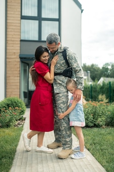 Strong heroic husband. dark-haired wife wearing red dress standing near her strong heroic husband and daughter