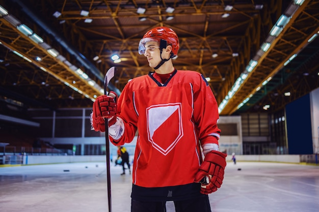 Strong hockey player standing on the ice in hall and holding a stick.