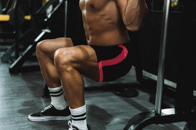 Strong legs of a caucasian adult man squatting with weights in a gym