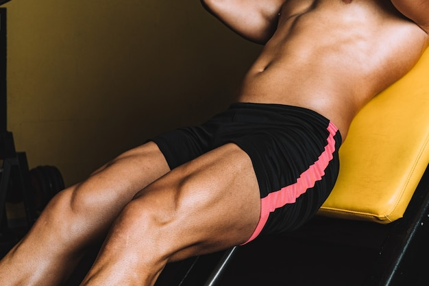 Strong legs of a man in shorts exercising in the gym