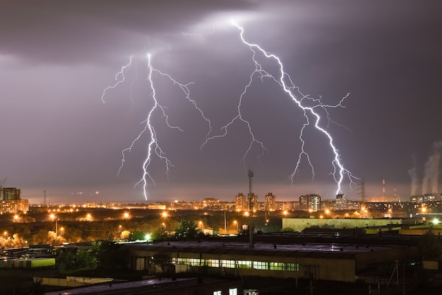 Strong lightning flash in the night sky above the city