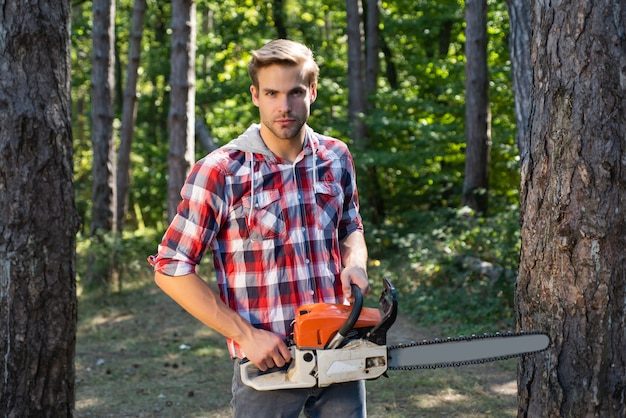 Strong lumberjack with an axe or chainsaw in a plaid shirt lumberjack on serious face carries chains...