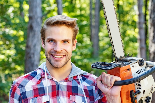 Strong lumberjack with chainsaw in a plaid shirt. lumberjack worker walking in the forest with