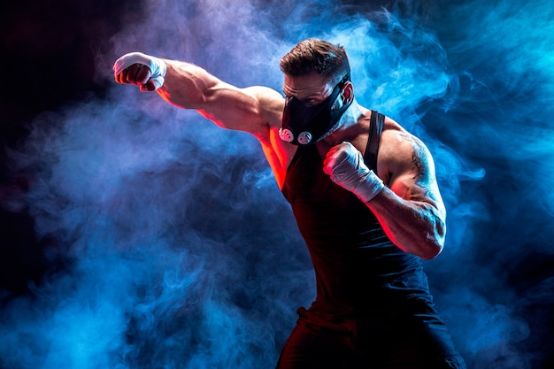 Strong male athlete in a black training mask on a black wall