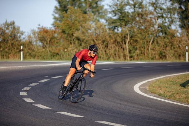 포장 도로에서 고속으로 헬멧, 안경 및 활동복 승마 자전거에 강한 남성 운동 선수