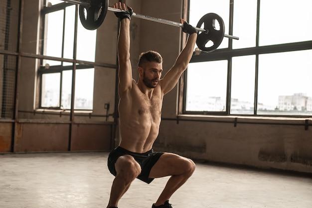 체육관에서 운동하는 동안 날치기 운동을하는 머리 위로 무거운 바벨을 들어 올리는 강한 남성 운동 선수